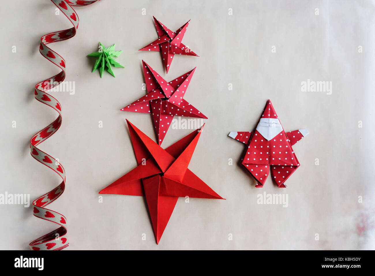 overhead of handmade origami christmas ornaments and ribbon on paper background subject capture against soft - Handmade Paper Christmas Decorations