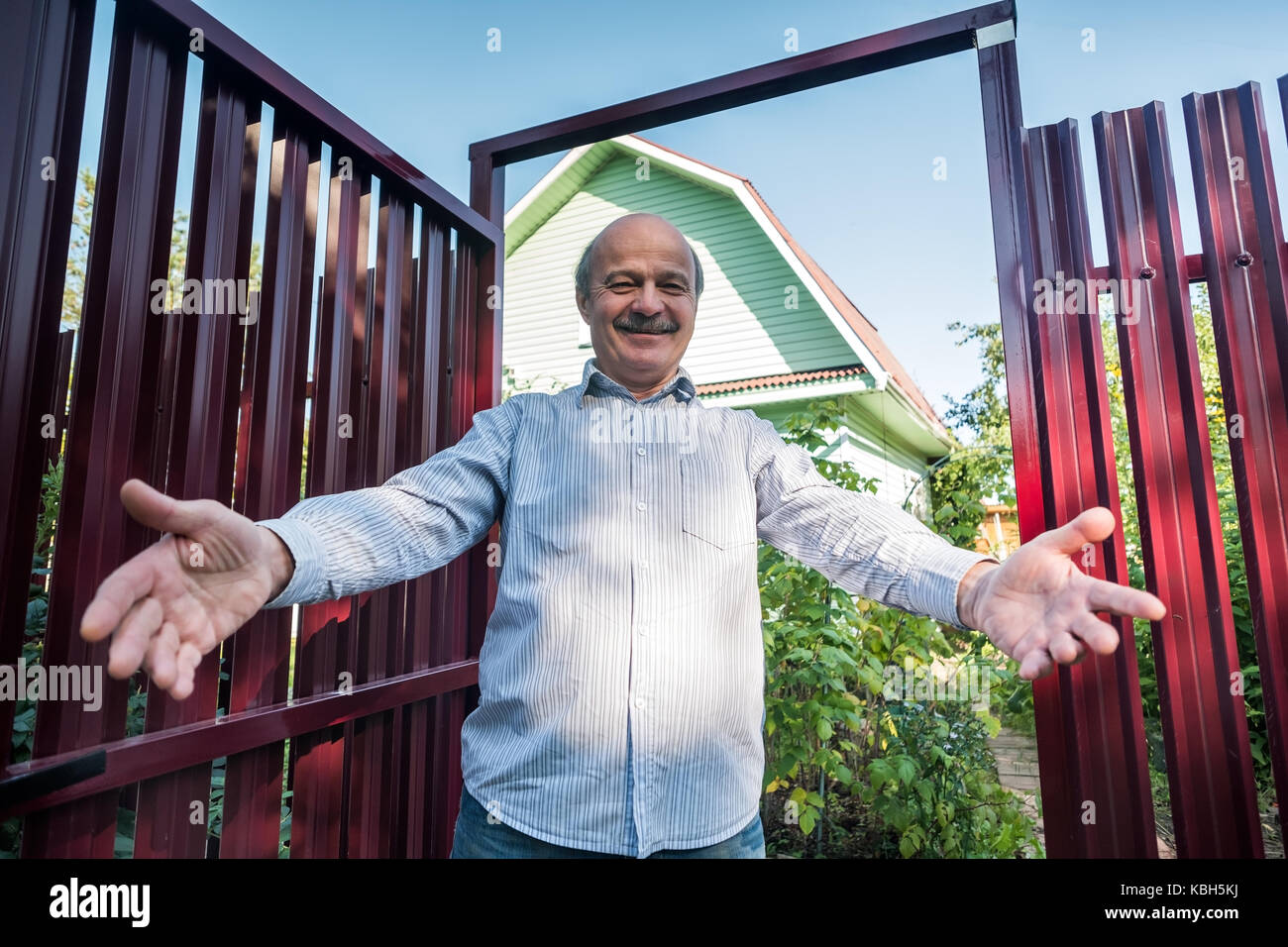 An elderly man meets guests at a red metal fence waiting for guests. - Stock Image