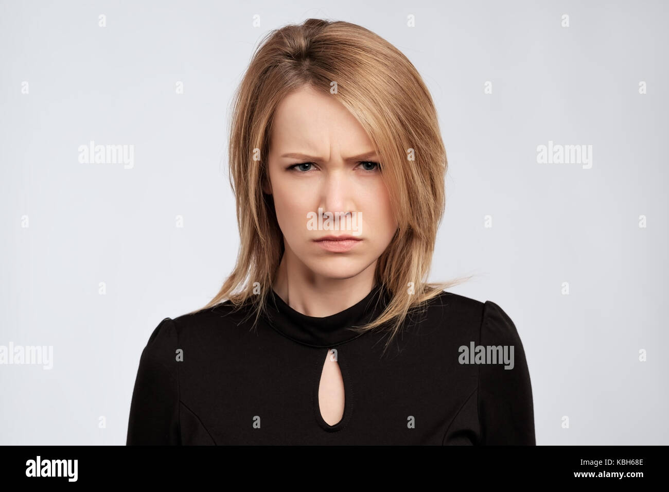 portrait of young serious angry woman with blond hair - Stock Image