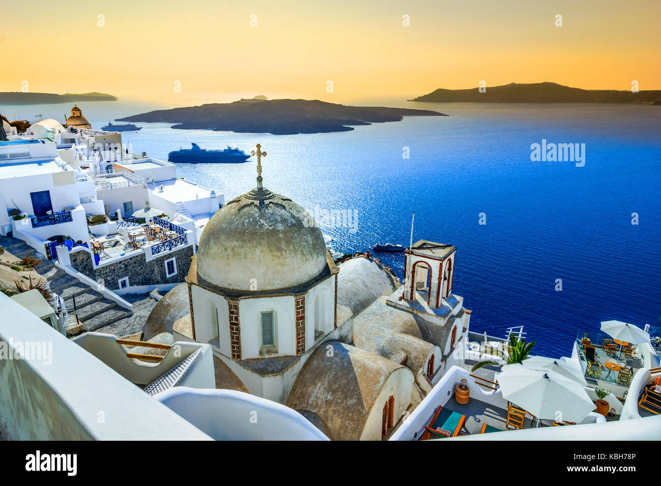 Fira, Santorini - Greek Islands landmark with white village, cobbled paths, greek orthodox blue church and sunset - Stock Image