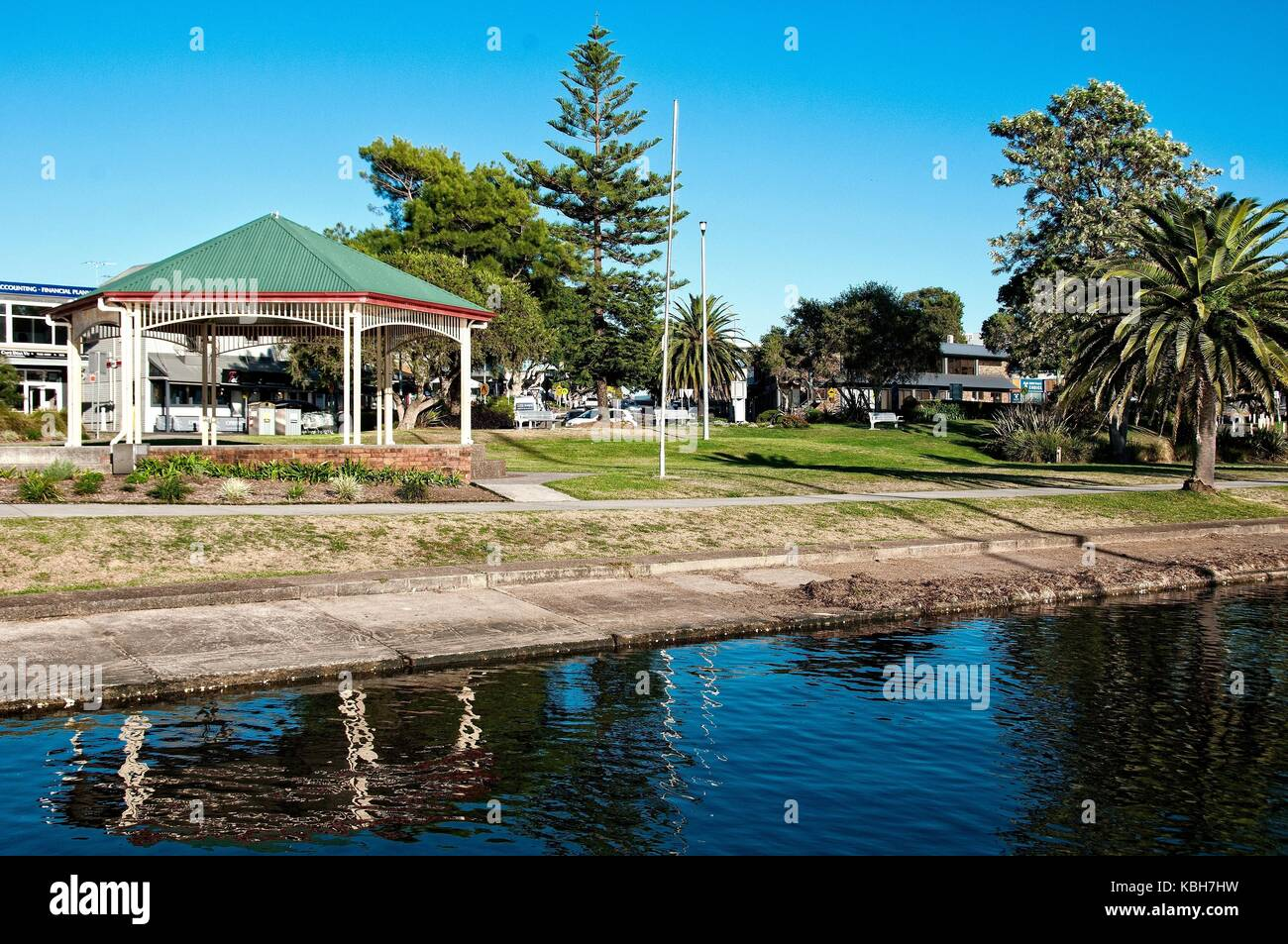 Picturesque green grassy lake waterfront park with a quaint old bandstand, trees, and water reflections in the tranquil - Stock Image