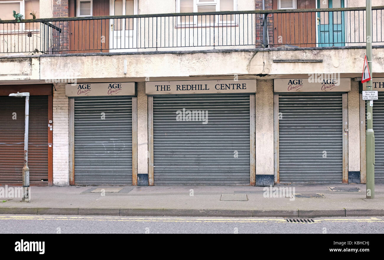 Age Concern and the Redhill Centre with metal shutters down in Redhill Surrey UK - Stock Image