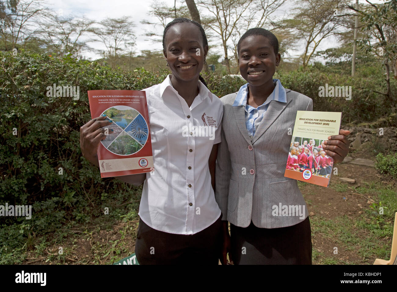 Two young African AFEW staff with new curriculum guides Kenya - Stock Image