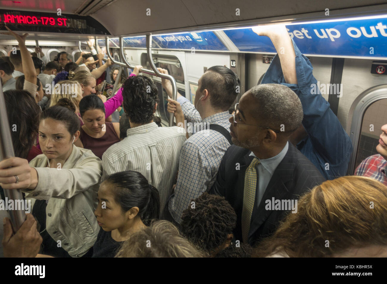 Very crowded F train on its way from Brooklyn to Manhattan during the morning rush hour in New York City. - Stock Image