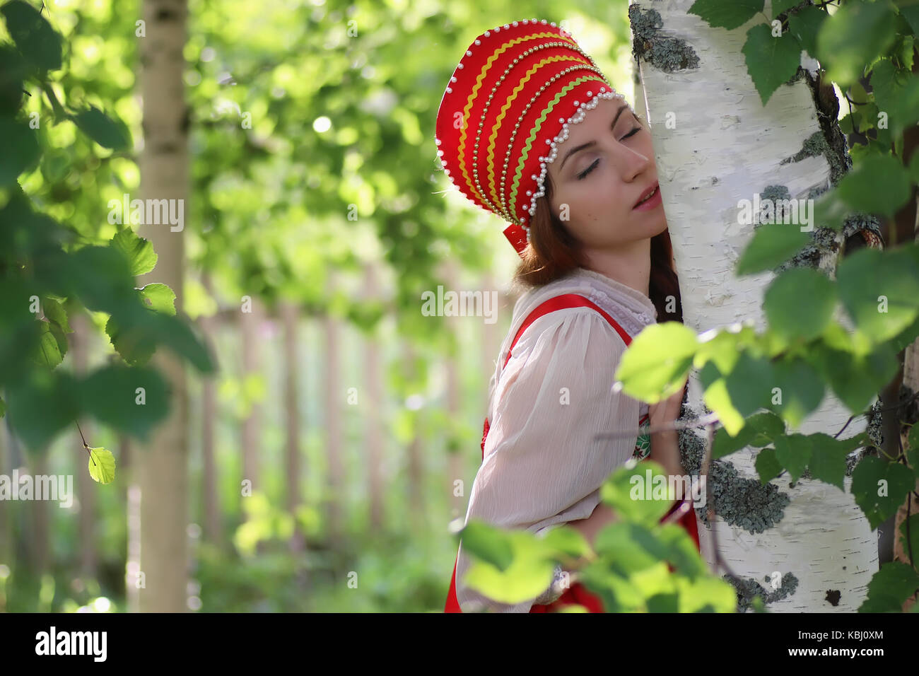Slav in traditional dress hiding behind trees - Stock Image