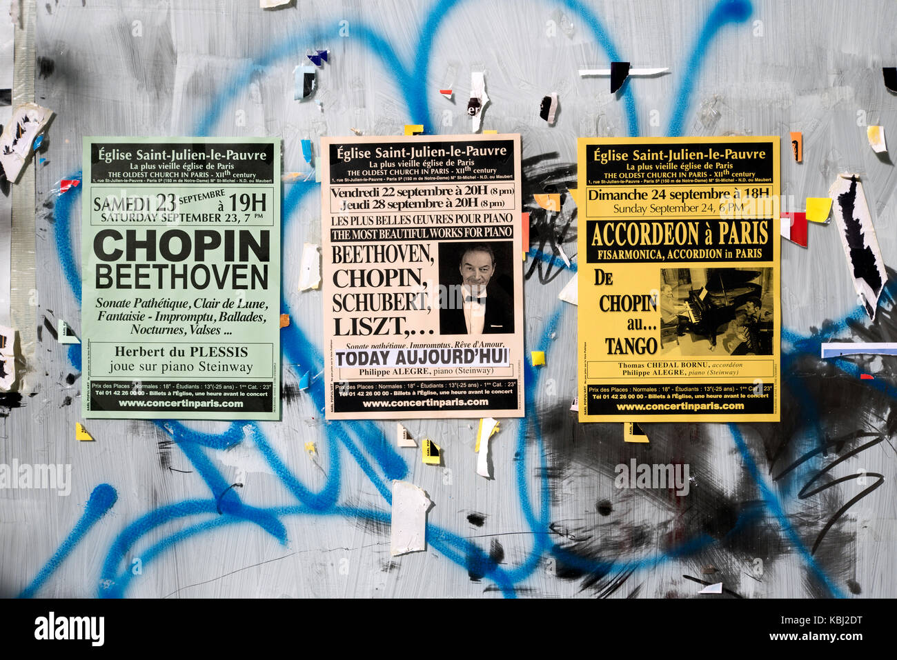 Adverts for a series of concerts to be held in Église Saint-Julien-le-Pauvre on a vacant shop window in the - Stock Image