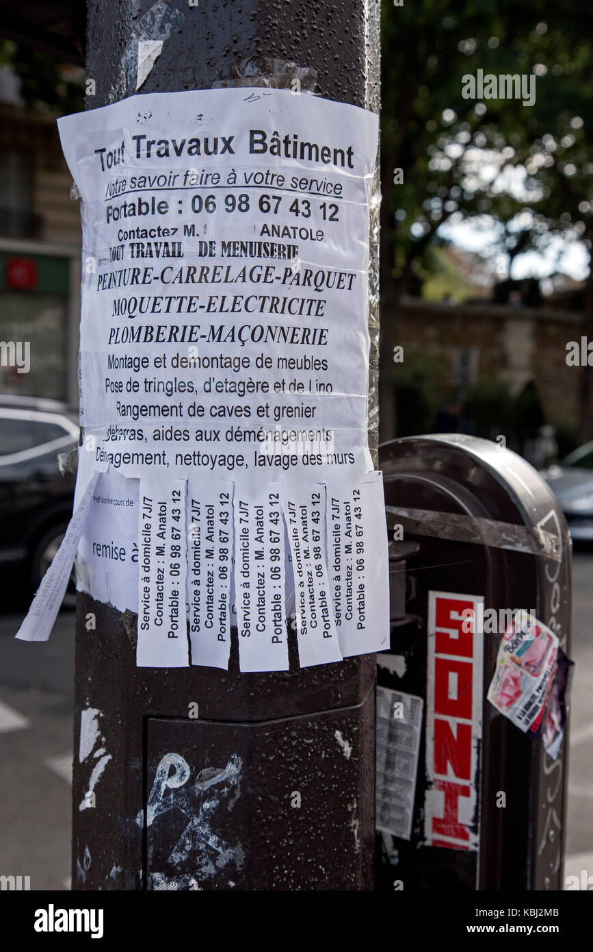 Handmade poster with tear off phone number strips on the Boulevard de Ménilmontant in Paris advertising the - Stock Image