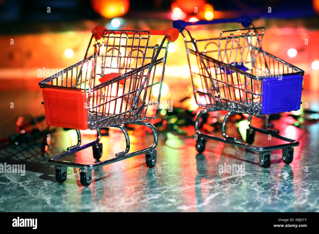 metal supermarket small cart on a background colored lights Stock Photo