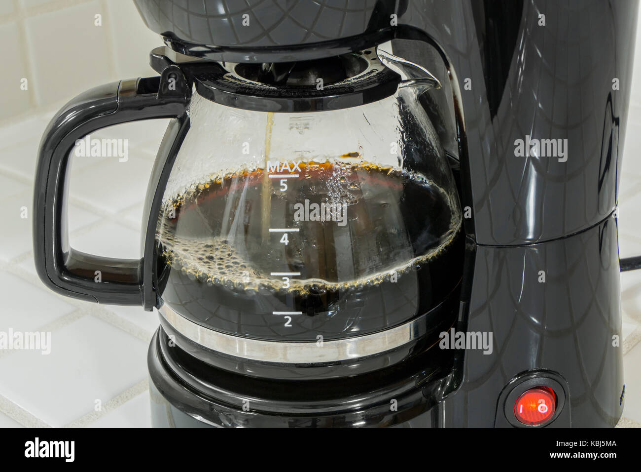 Coffee maker pot filling close up. - Stock Image