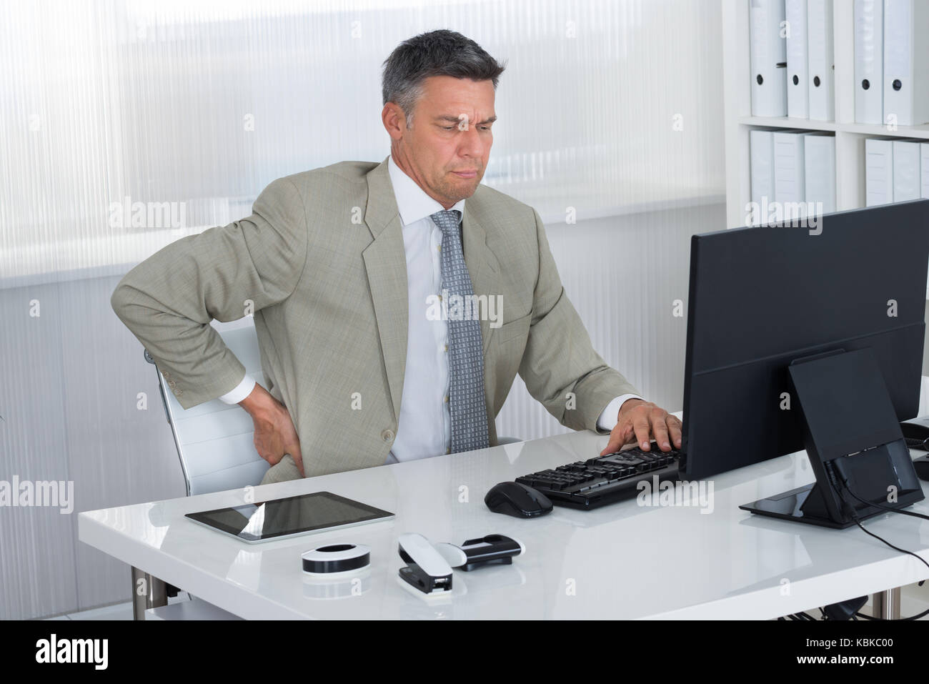 Mature businessman suffering from back pain at desk in office - Stock Image