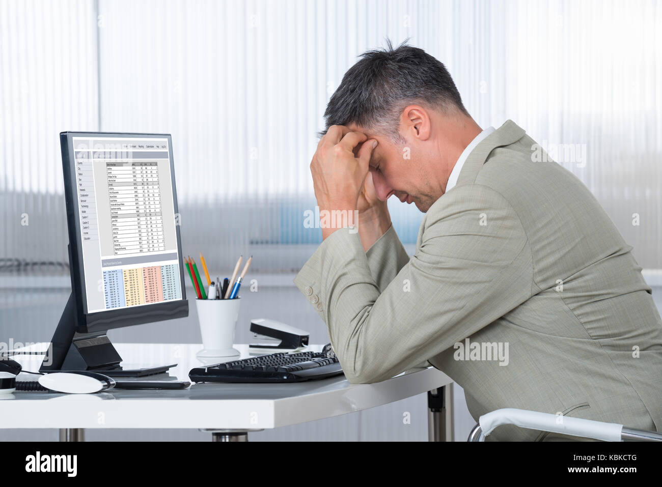 Side view of accountant suffering from headache at desk in office - Stock Image