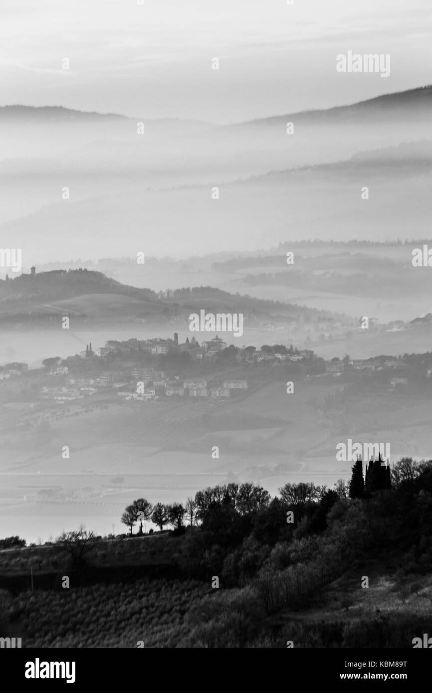 A valley filled by fog, with some hills and trees in the foreground and some towns emerging from the mist - Stock Image