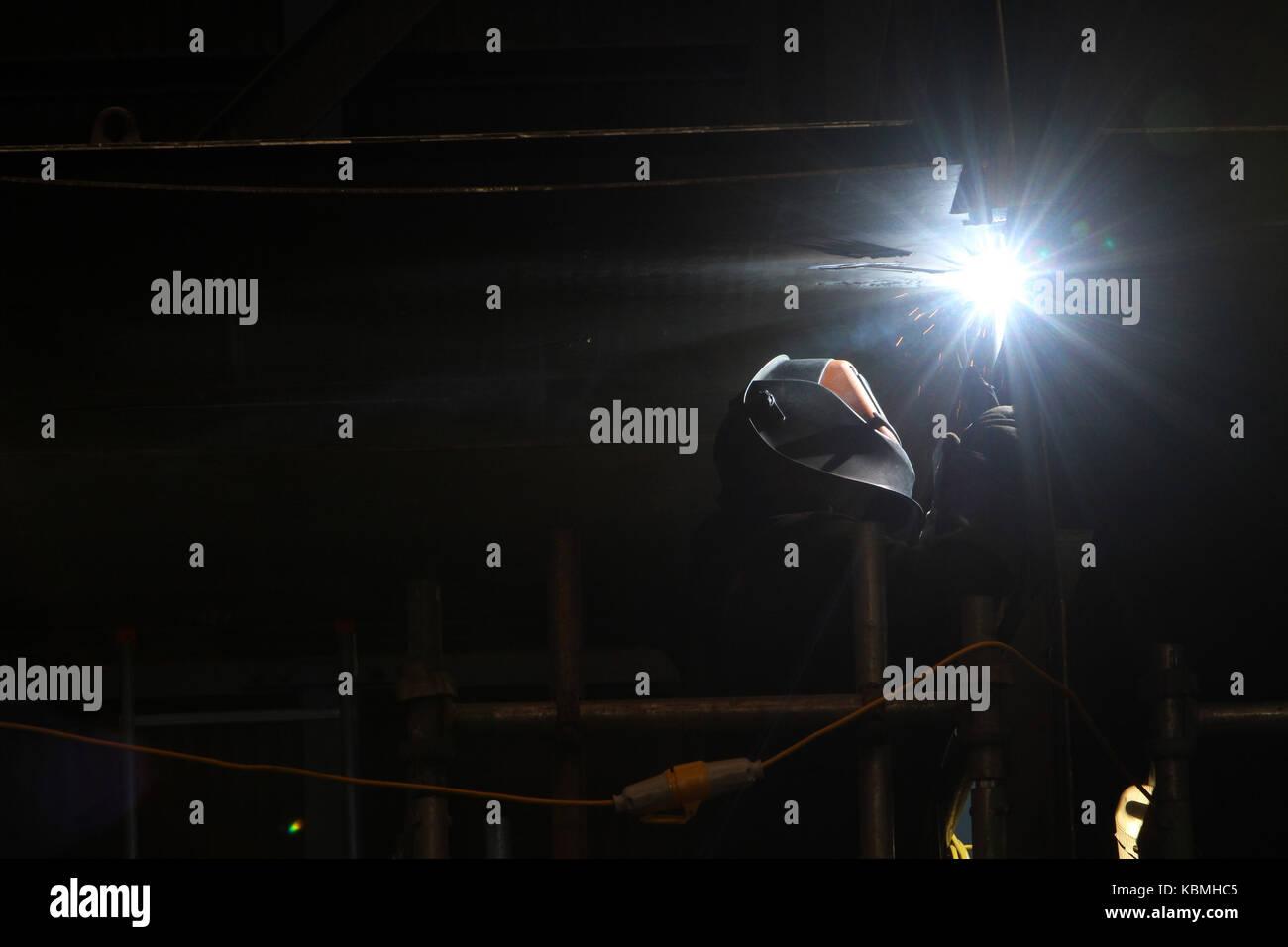 tradesman welding in shipyard - Stock Image