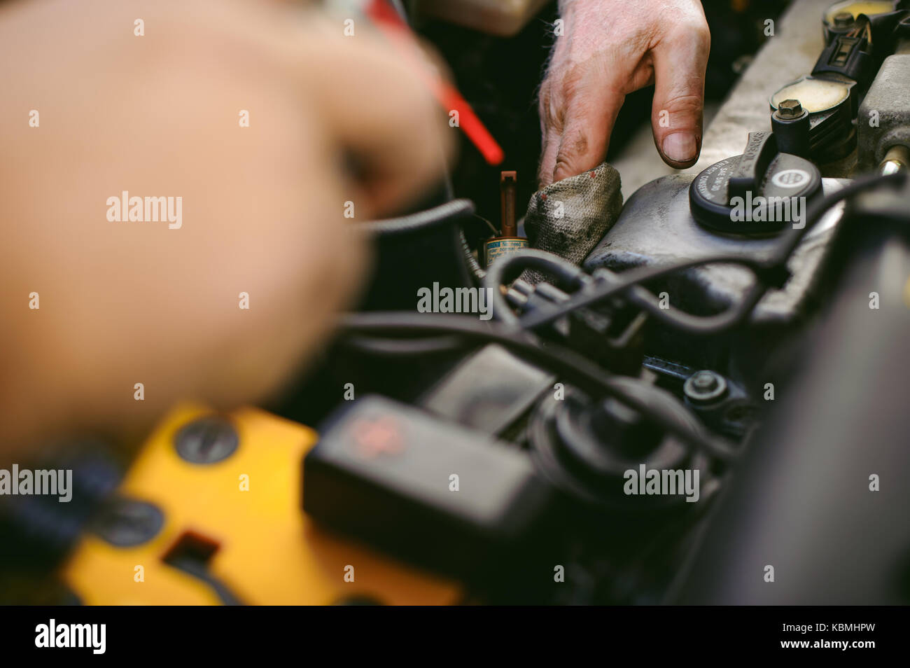 hands of an auto mechanic close-up. servicing and caring for a car engine - Stock Image