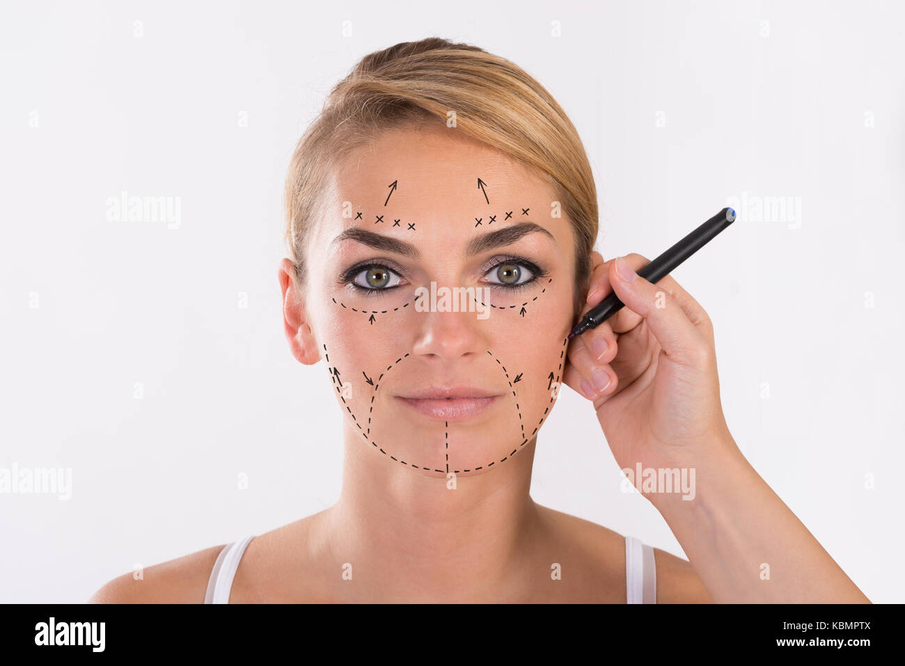 Portrait of young woman undergoing facelift surgery over white background Stock Photo