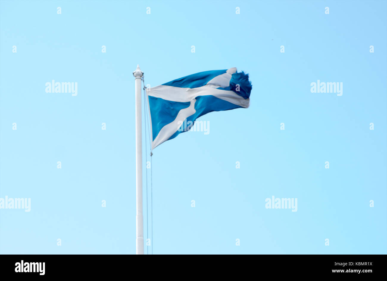 Scottish flag (Saltire) on a flagpole waving in the wind - Stock Image