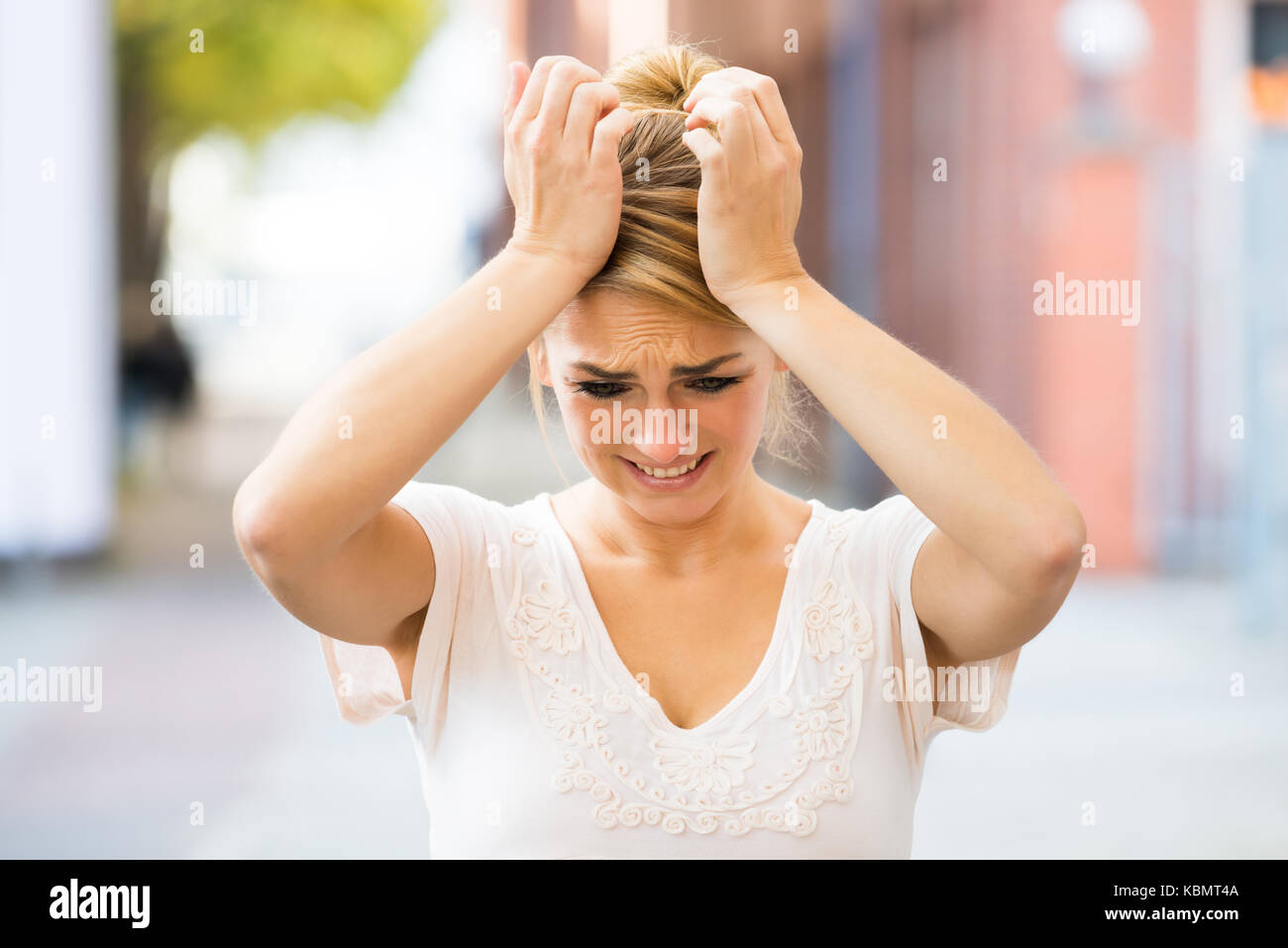 Sad young woman suffering from headache outdoors - Stock Image