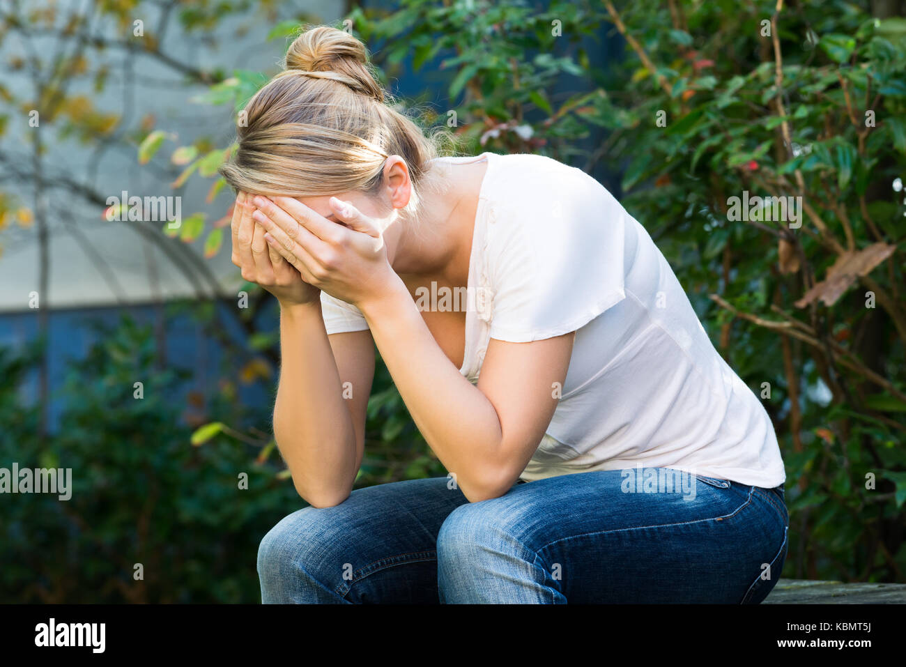 Tensed young woman covering face with hands - Stock Image