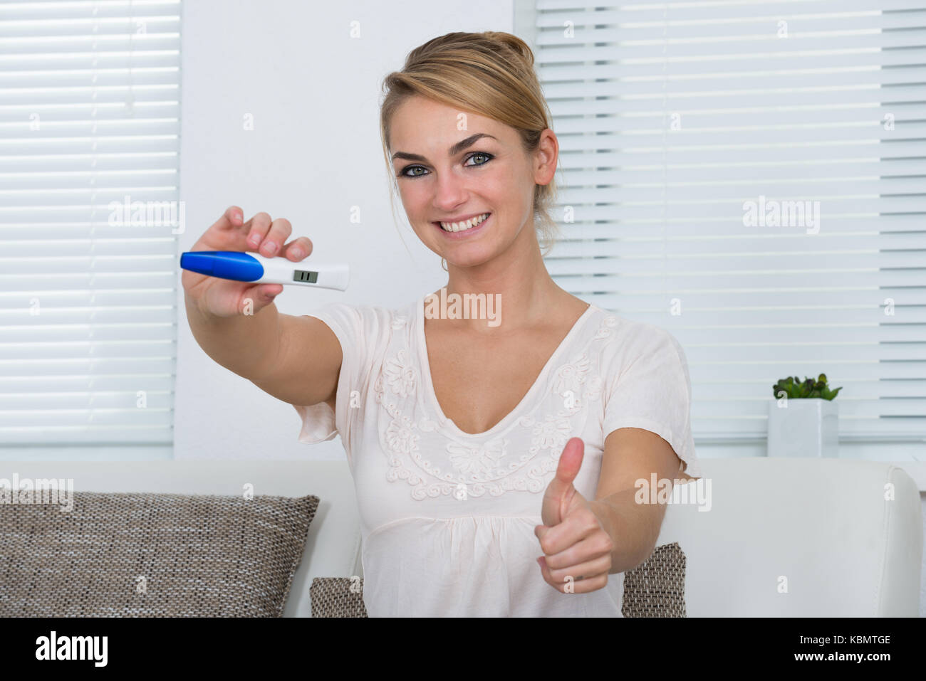 Portrait of happy young woman gesturing thumbs up while showing positive pregnancy result at home - Stock Image