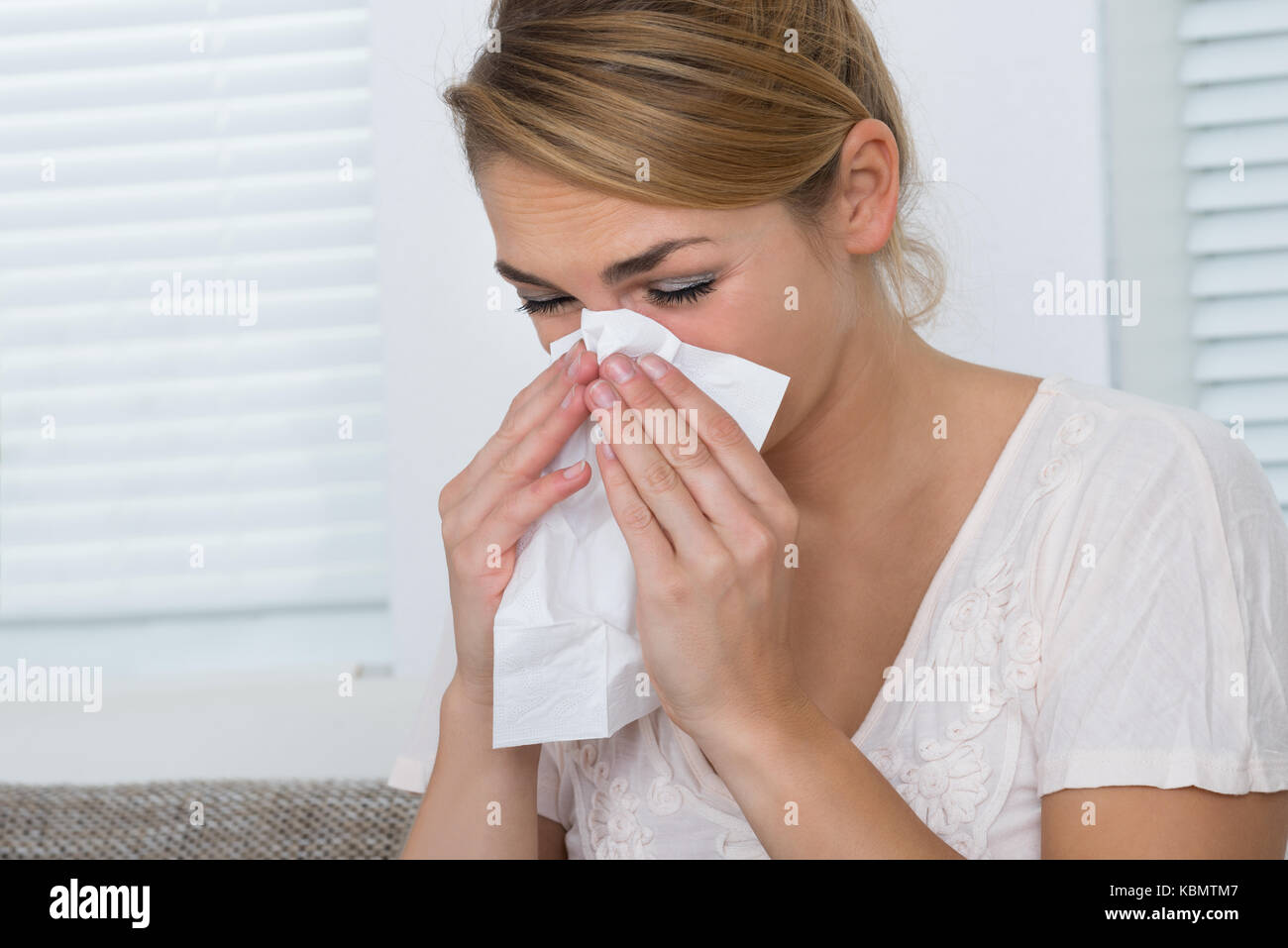 Young woman blowing nose while suffering from cold at home - Stock Image