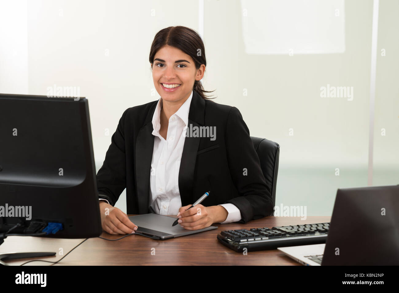 Young Happy Female Designer With Graphic Tablet Sitting At Desk - Stock Image