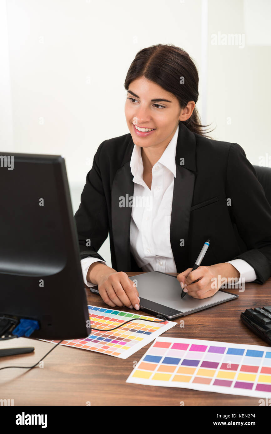 Female Designer Using Graphic Tablet With Color Sample At Desk - Stock Image
