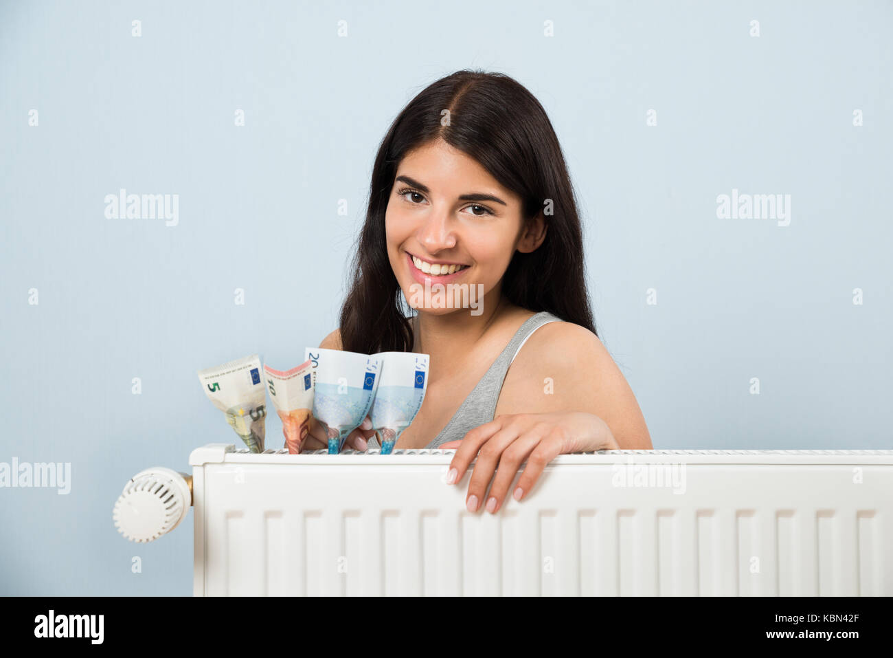 Young Happy Woman With Banknote Inside White Radiator - Stock Image