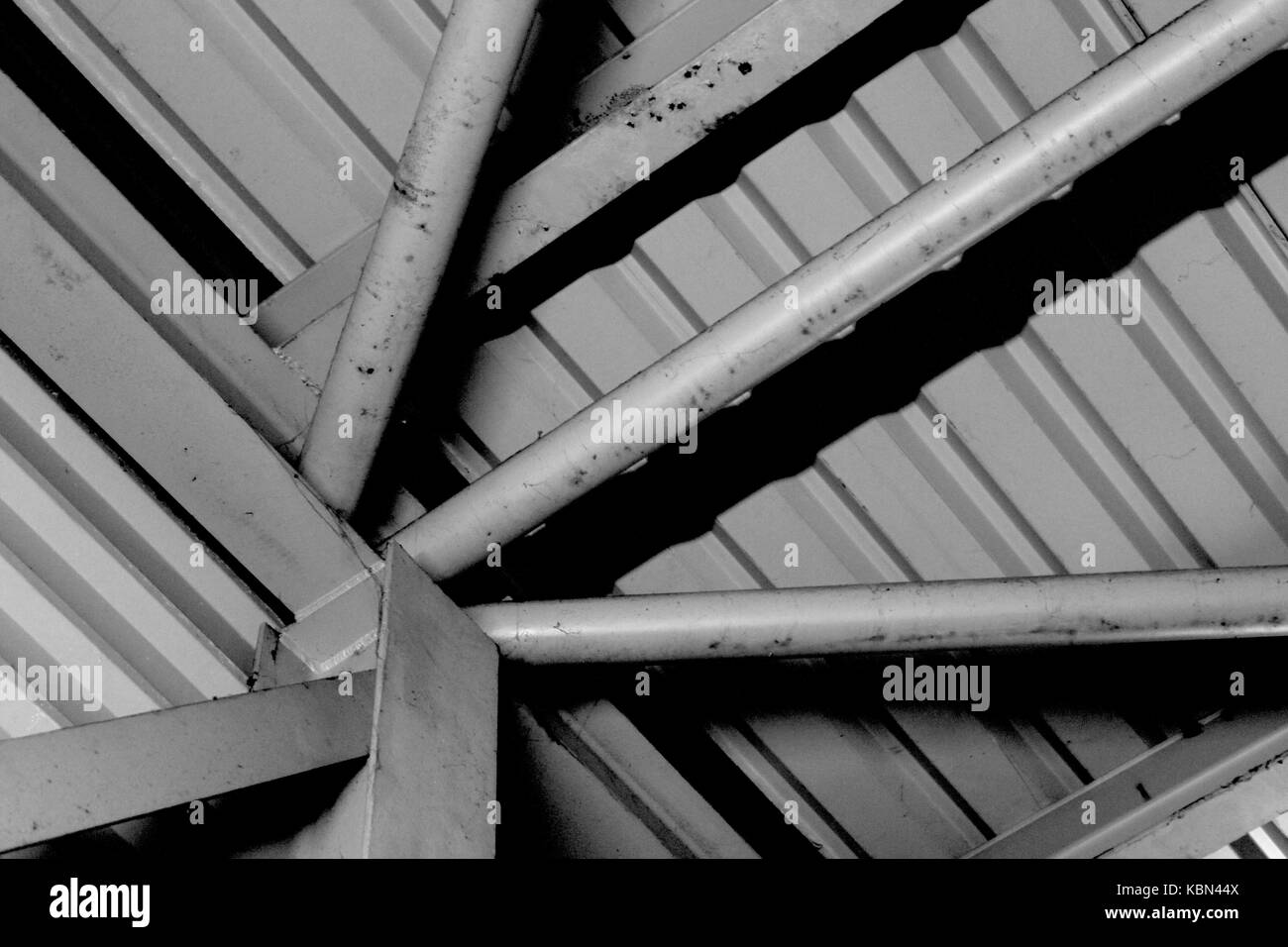 Formalist photography simple black and white photograph of metal industrial architecture with a sunburst of metal girders converging bottom left