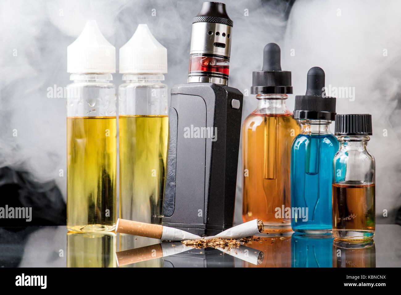 Modern vaporiser versus old tobacco cigarette in smoke cloud Stock Photo