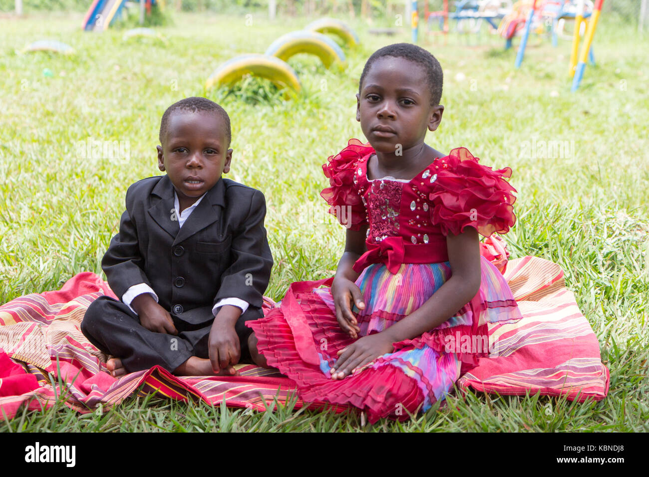 African boy and girl sitting together on a blanket in the grass. Both are dressed formally. - Stock Image