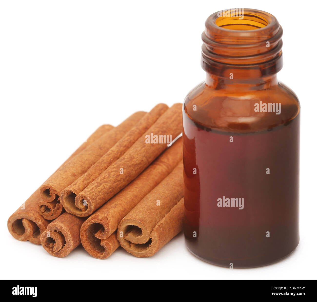 Bunch of some fresh aromatic cinnamon with essential oil in a bottle - Stock Image