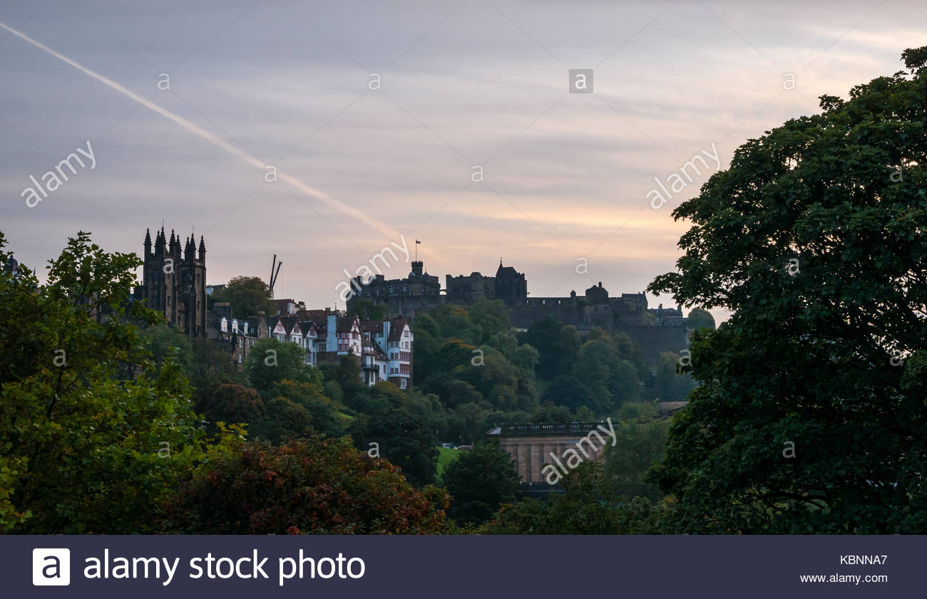 Evening sky through trees at dusk, Edinburgh Castle on rocky outcrop, old buildings on Royal Mile and Assembly Hall - Stock Image