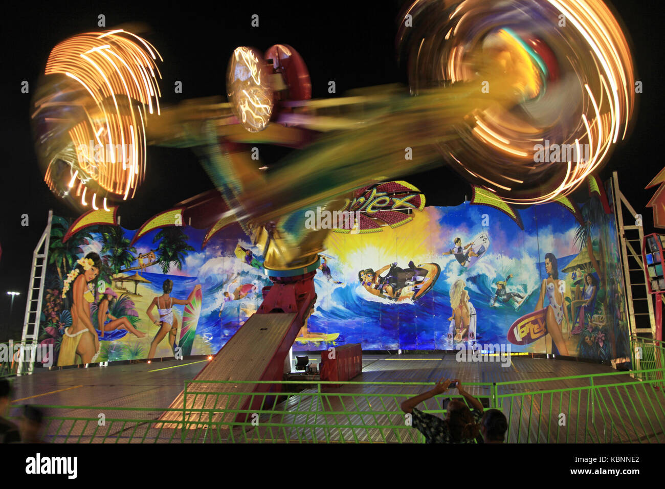 A thrill ride spins and turns at night - Stock Image