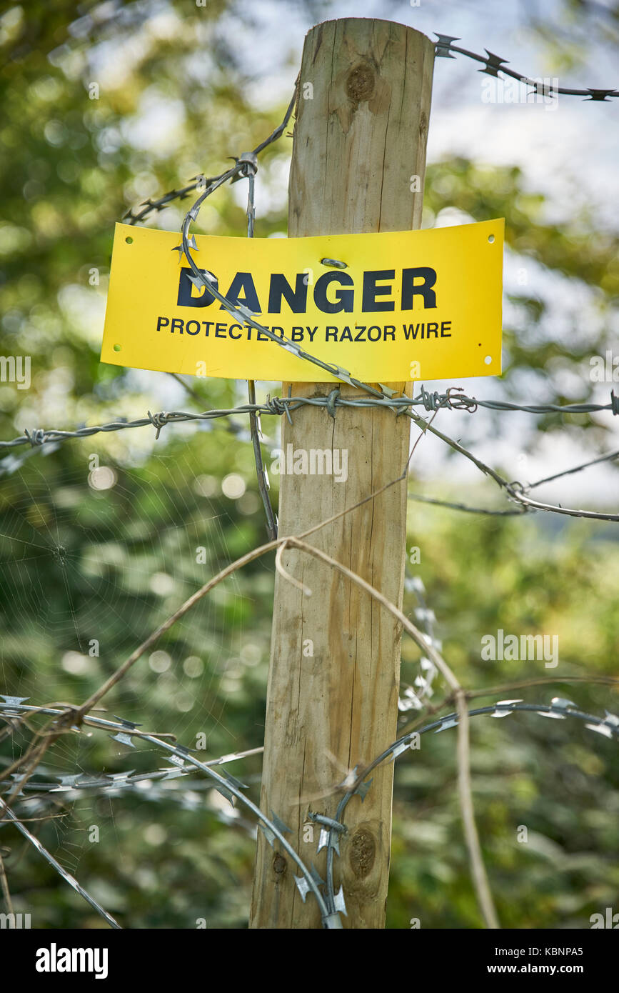 Yellow Danger Sign with Razor Wire - Stock Image