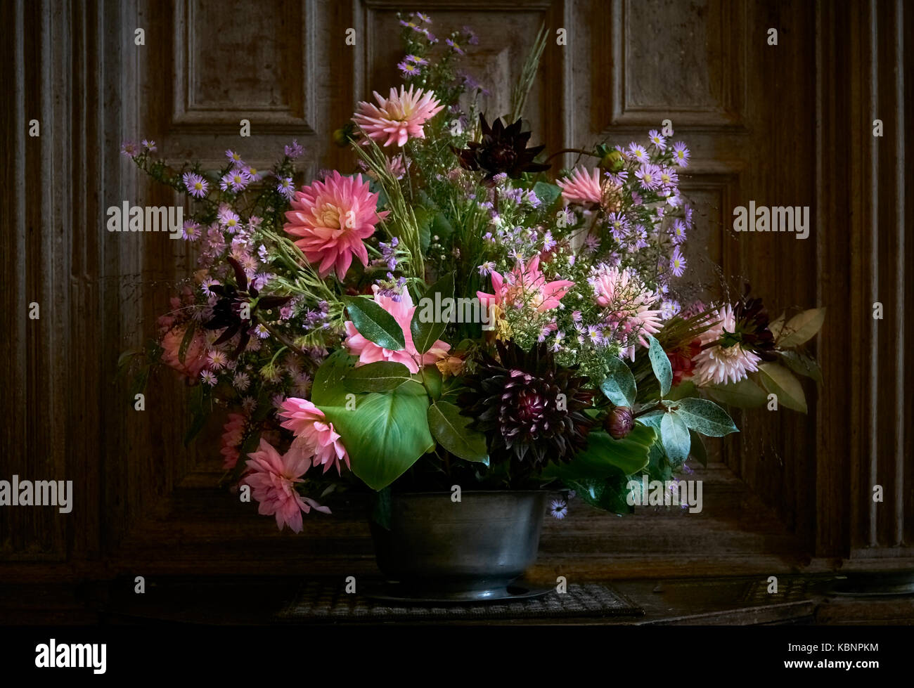 Autumn Flower Arrangement In A Rustic Pewter Vase Indoors Front Of Oak Panelling