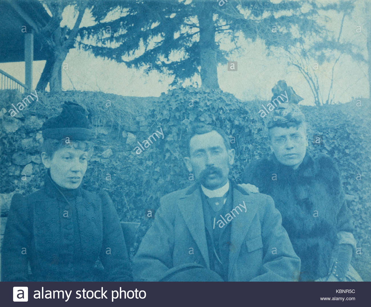 American archive cyanotype portrait photograph of a man with moustache and two women. They are sitting outside with - Stock Image