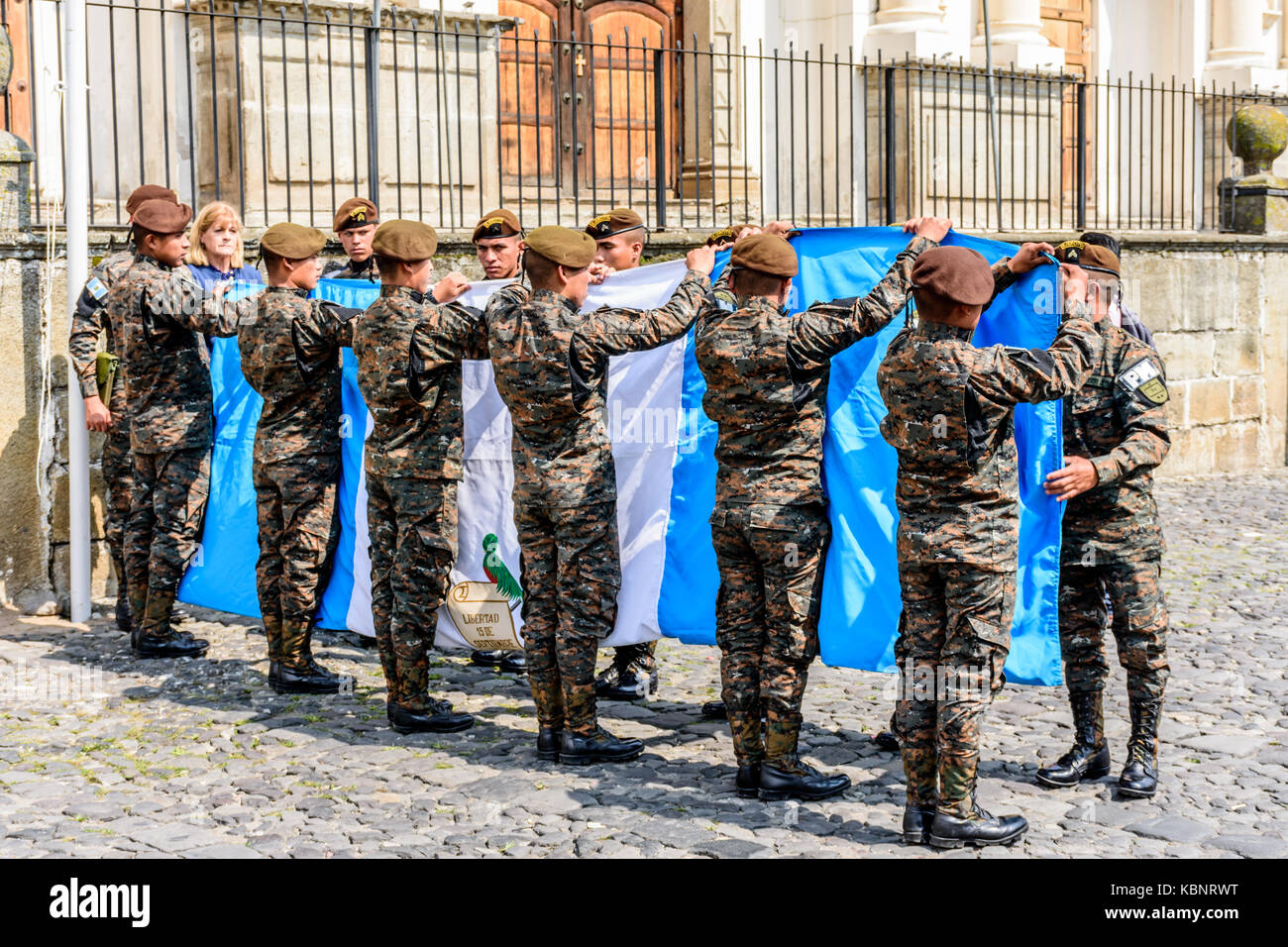 Antigua, Guatemala - September 15, 2017: Soldiers fold Guatemalan flag with Mayor of Antigua after lowering it on - Stock Image