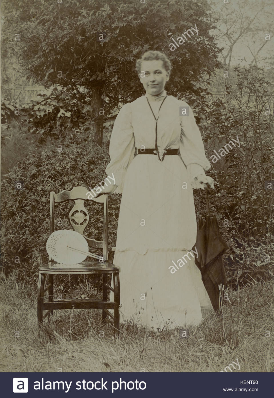 American archive monochrome photo of a young woman or girl standing next to a chair in a garden A fan is on the Stock Photo
