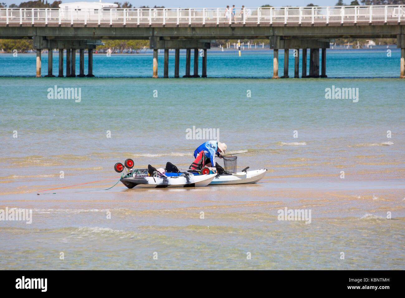 Man fishing off a sandbar in Wallis Lake at Forster on the mid north coast of new south wales,australia - Stock Image
