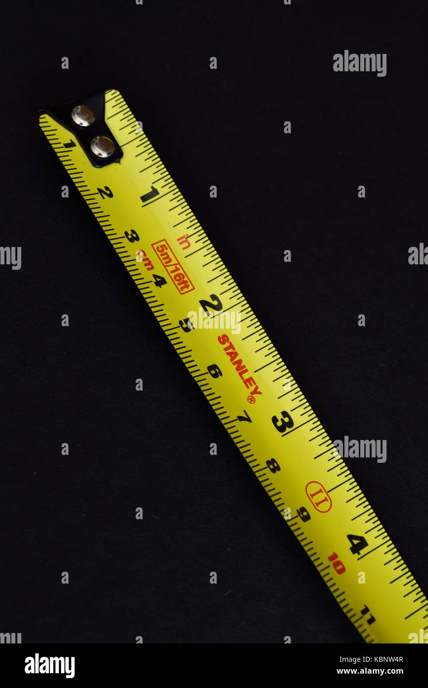 Yellow Stanley steel tape measure on black background. - Stock Image