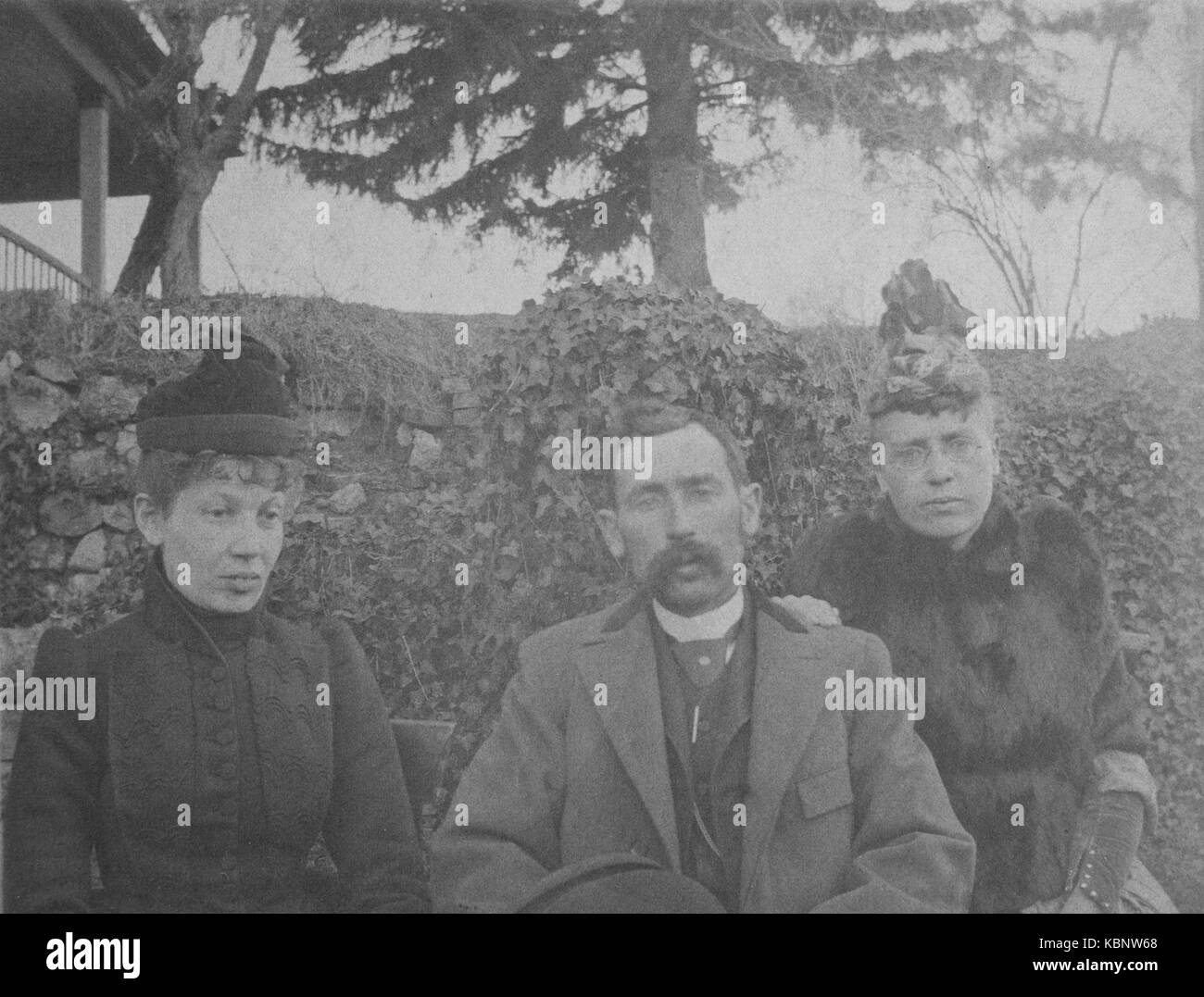 American archive monochrome version of cyanotype portrait photograph of a man with moustache and two ladies sitting - Stock Image
