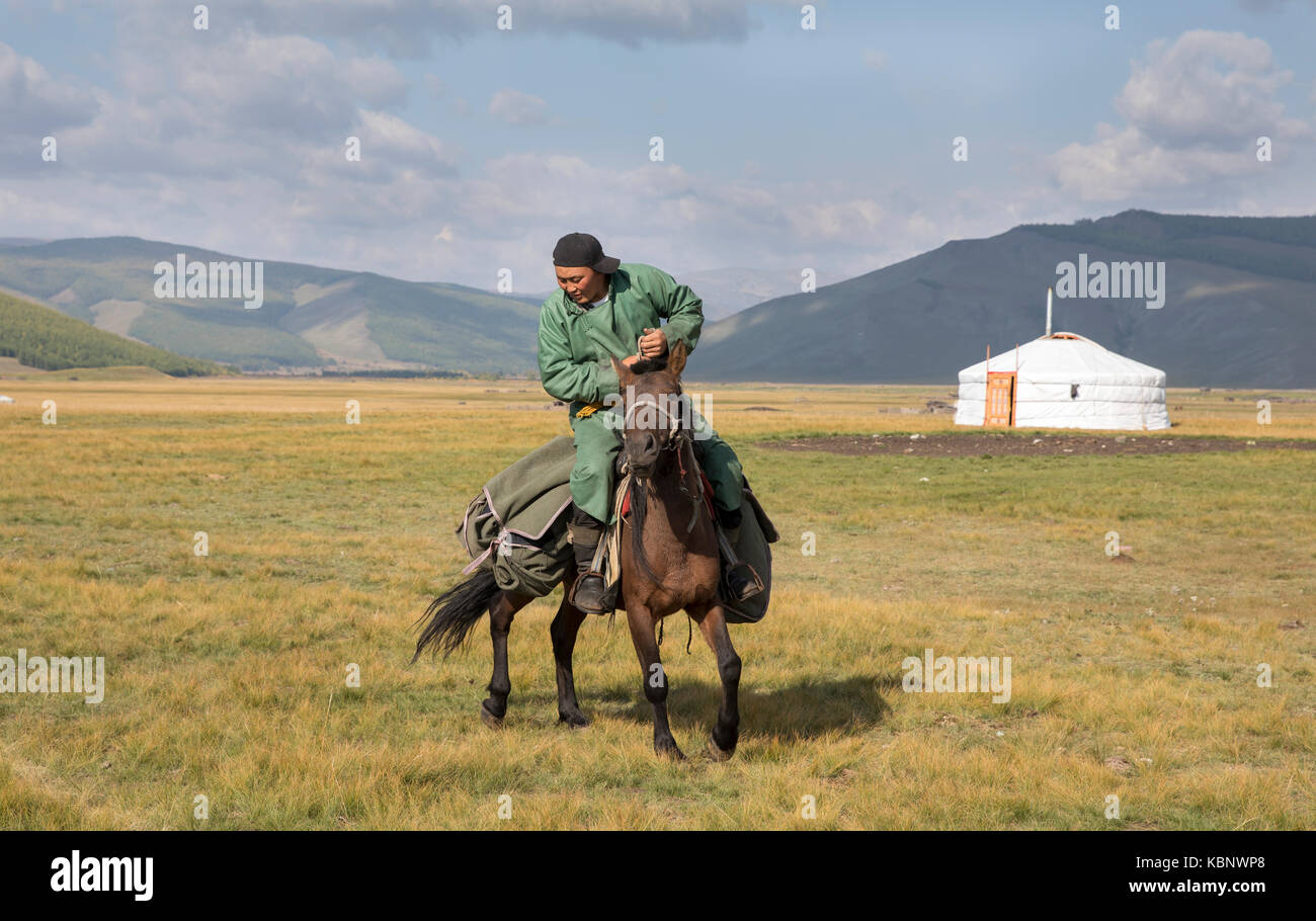 Huvsgul, Mongolia, September 6th, 2017: mongolian man riding a horse in northern mongolian landscape - Stock Image