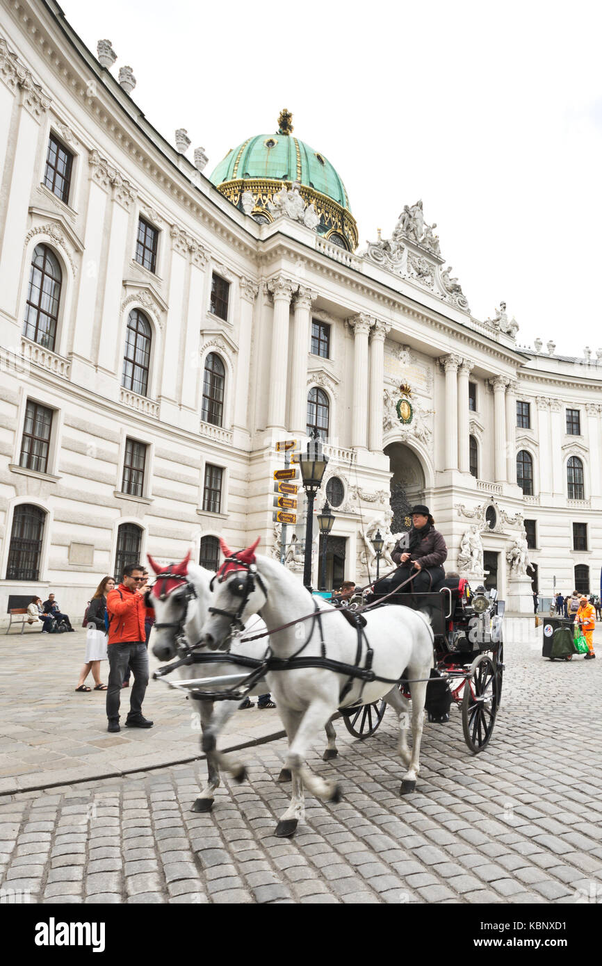 Famous horse-drawn carriage called fiaker passes by the Hofburg palace at Michaelerplatz in Vienna with tourists Stock Photo