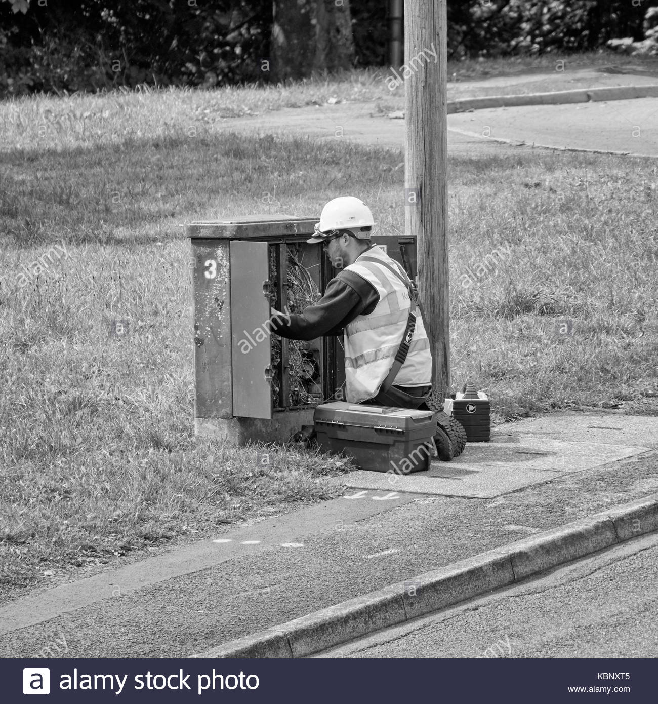 an engineer on his knees repairing or modifying a telephone junction box in baglan south wales uk - Stock Image