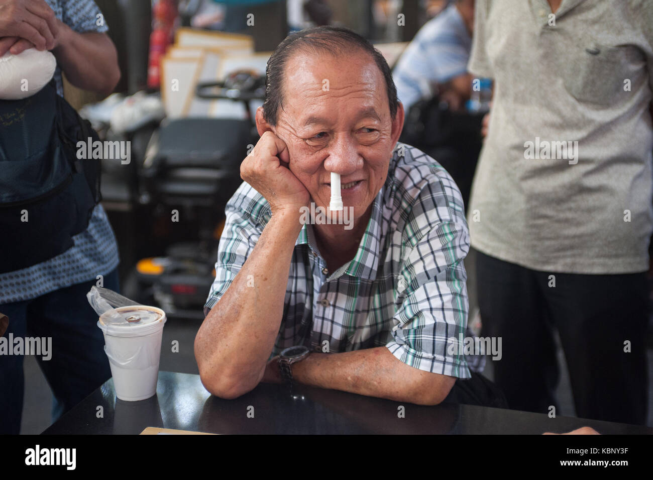 29.09.2017, Singapore, Republic of Singapore, Asia - An elderly man with a blocked nose sits at a table at a public - Stock Image