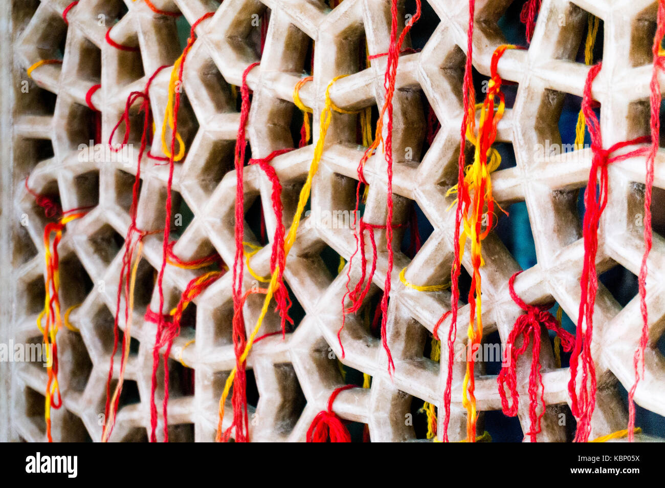 Marble mesh covered with sacred multicolored threads. These threads are tied to the mosque by people who want their - Stock Image