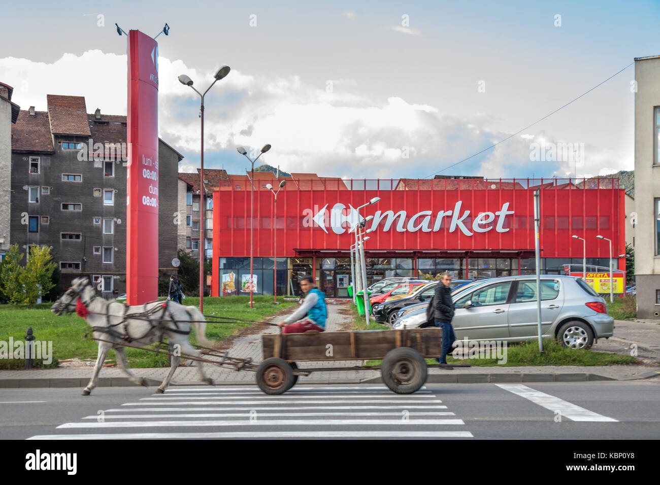 PETROSANI, ROMANIA - SEPTEMBER 23, 2017: Horse Cart driven by people from Roma community passing in front of a Carrefour - Stock Image