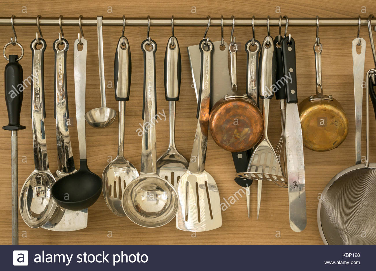 Batterie de cuisine, kitchen spoons, ladles, copper saucepans, fish slices, knife sharpening steel and kitchen utensils - Stock Image