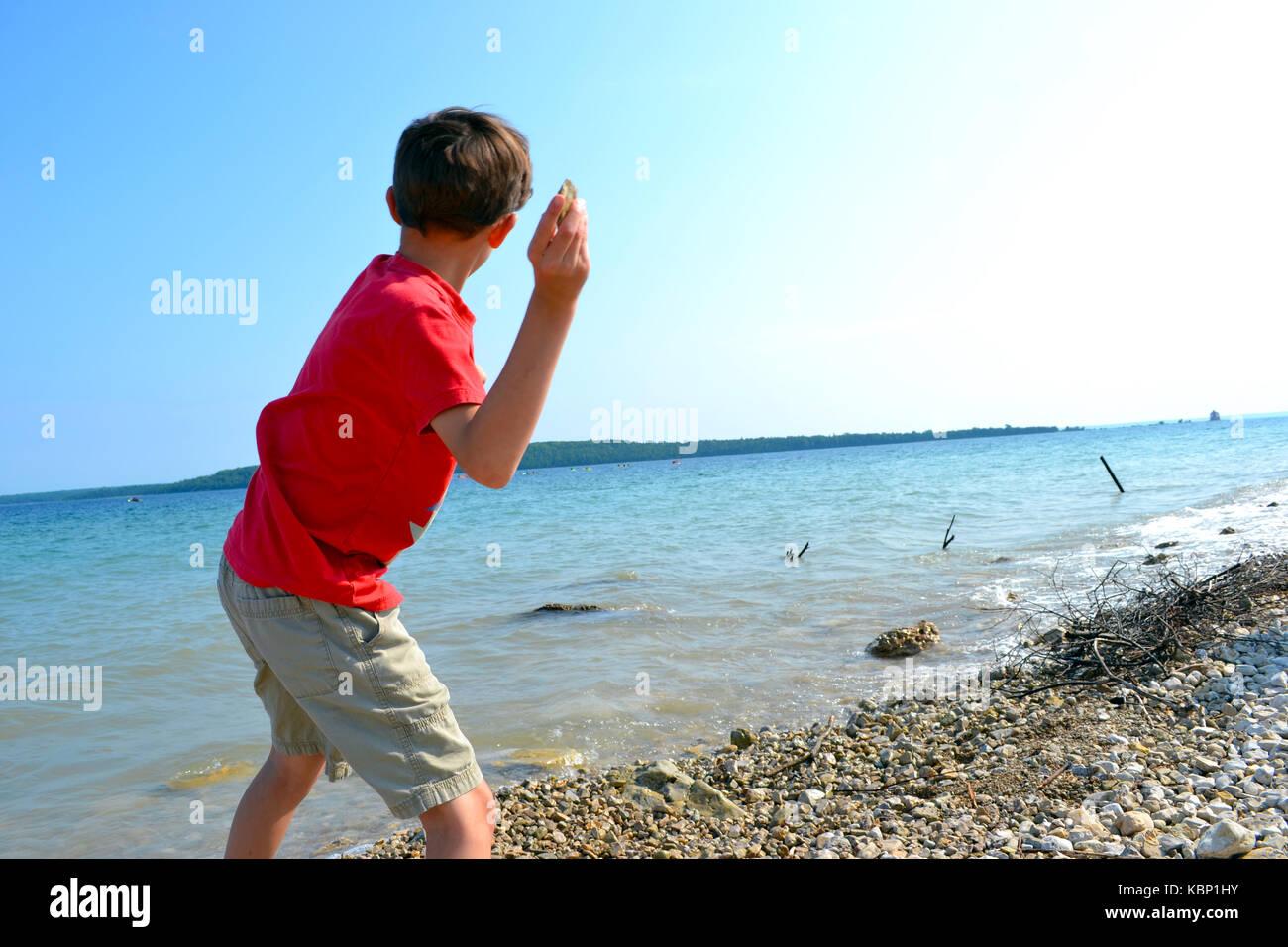 Boy skipping stones - Stock Image