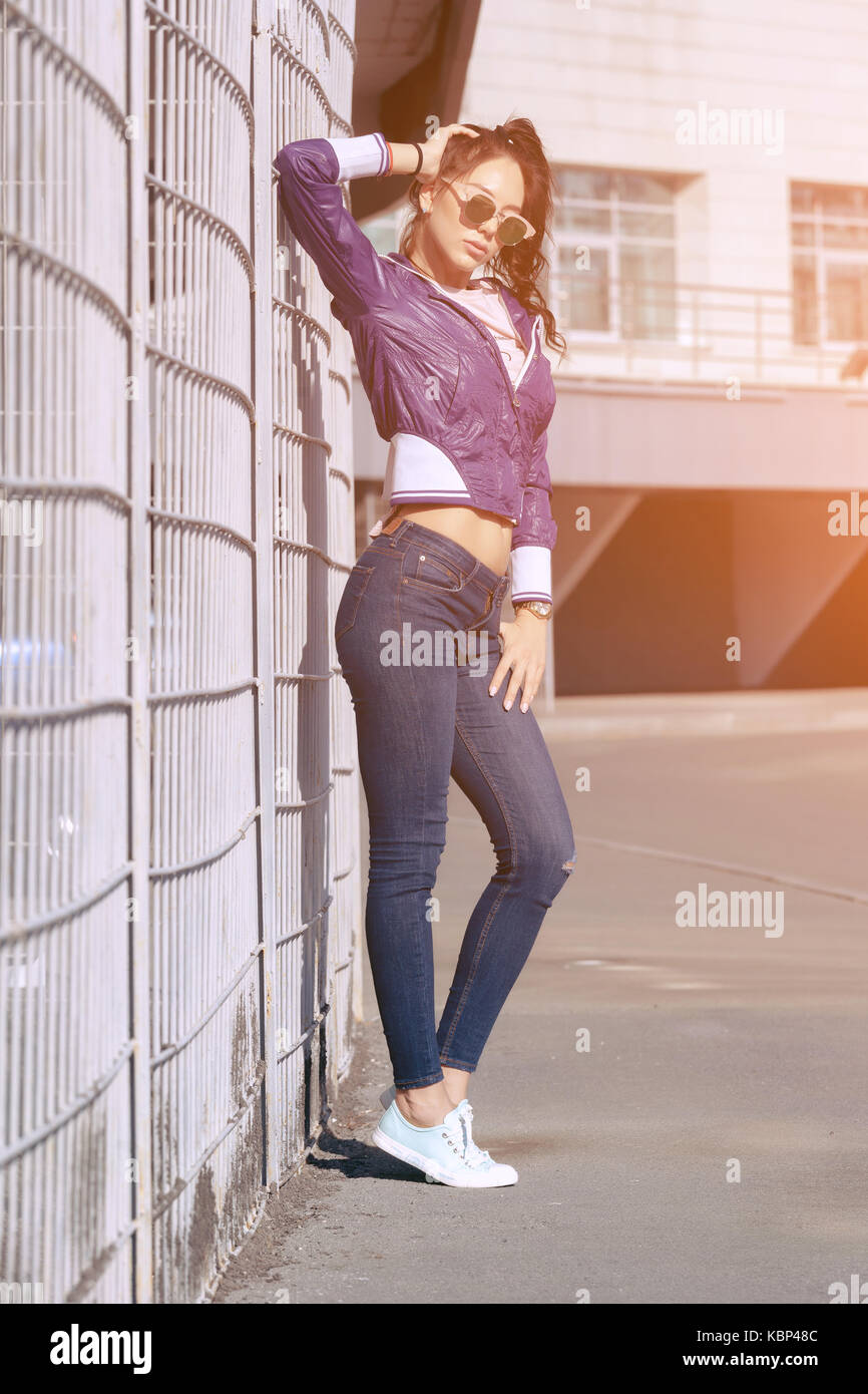 Fashionable young woman in sunglasses, lilac short windbreaker and jeans. on the background of large air conditioners. - Stock Image